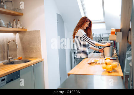 Beautiful woman squeezing oranges in order to prepare homemade juice - Stock Photo