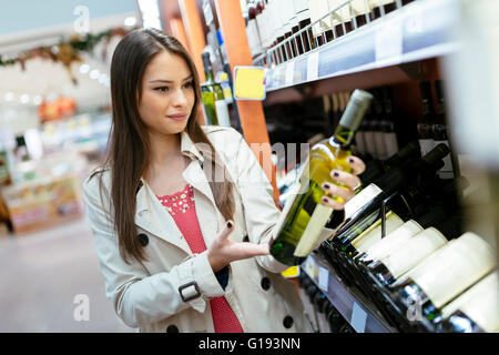 Woman deciding what wine to buy and shopping in supermarket - Stock Photo