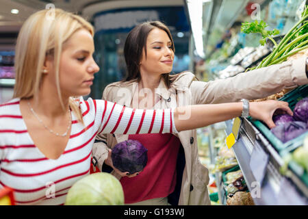 Beautiful women shopping vegetables and fruits in supermarket - Stock Photo