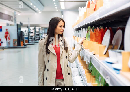 Beautiful woman shopping tableware in supermarket - Stock Photo