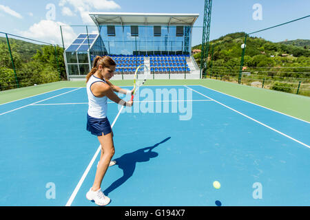 Female tennis player performing a drop shot on a nice blue court - Stock Photo