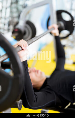 Closeup of young handsome male doing exercises on a bench press - Stock Photo