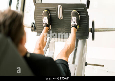 Young male working out in a gym and doing leg exercises - Stock Photo