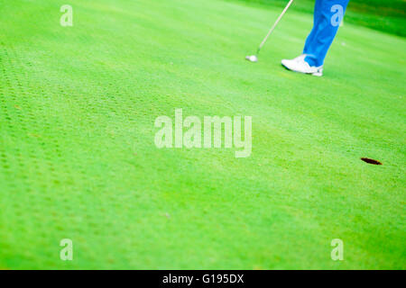 Golfer ready to take the shot on the putting green - Stock Photo