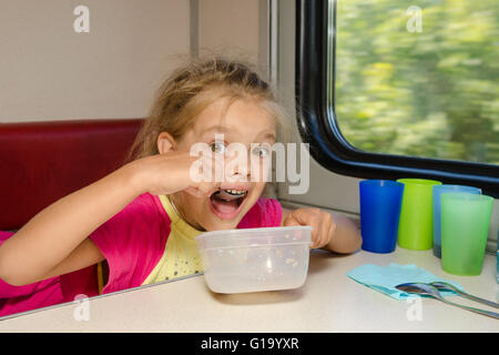 The girl on the train sits at a table on the lower place in the second-class compartment of the car and eats it - Stock Photo