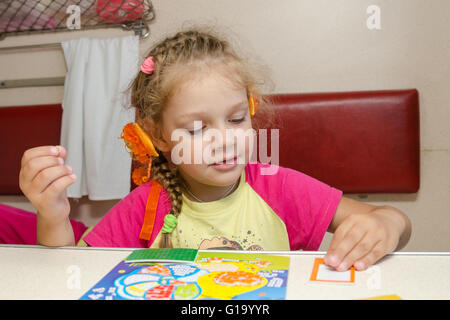 Little girl on the train sits at a table on the lower second-class place car and enthusiastically skin application - Stock Photo