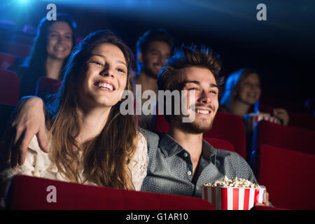 Young loving couple at the cinema watching a movie and smiling, people sitting on background - Stock Photo