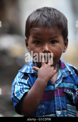 Pune, India - July 16, 2015: A portrait of a poor Indian boy putting fingers in his mouth. - Stock Photo