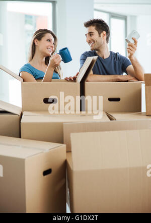 Happy couple having a coffee break during a relocation in their new house, they are holding a mug and smiling at - Stock Photo