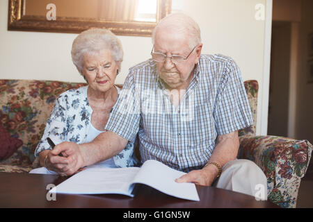 Portrait of a retired couple looking over documents while sitting at home. Senior caucasian man and woman sitting - Stock Photo
