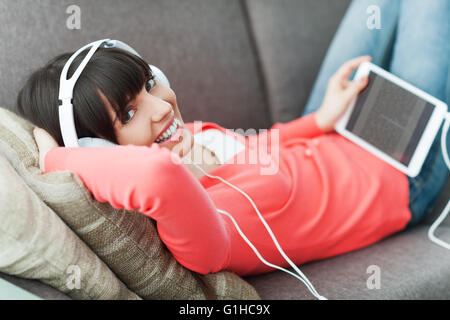 Smiling young woman relaxing at home on the couch, she is wearing headphones, using a digital tablet and watching - Stock Photo