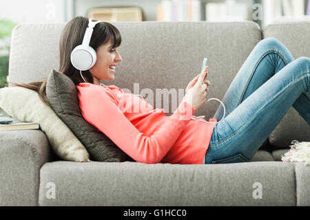 Attractive young woman on the sofa at home, she is playing music with her smarphone and wearing headphones, leisure - Stock Photo