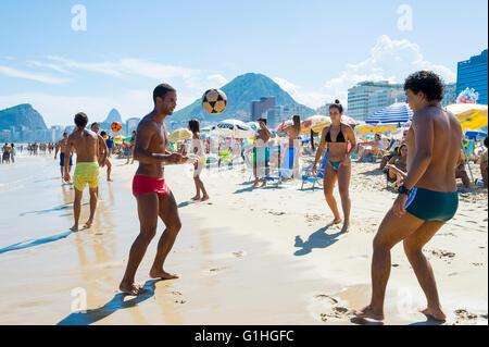 RIO DE JANEIRO - FEBRUARY 27, 2016: Young Brazilians play a game of altinho beach football in a keepy uppy circle - Stock Photo