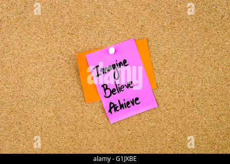 Imagine Believe Achieve written on paper note pinned on cork board with white thumbtack, copy space available - Stock Photo