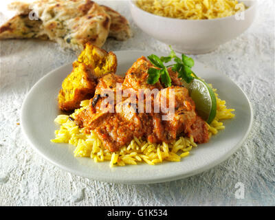Butter Chicken Asian curry with pilau rice and an onion bhaji - Stock Photo