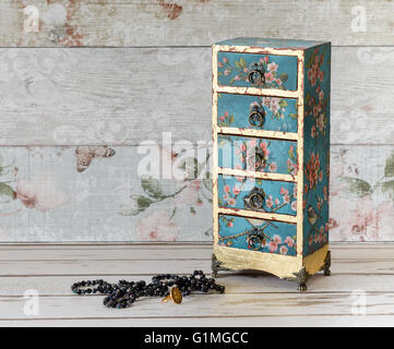 A beautiful handmade decoupaged jewelley box in a mini chest of drawers design on a rustic shabby chic background - Stock Photo