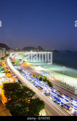 Dusk at Copacabana beach, view from above of  Copacabana promenade (calcadao) with Sugar Loaf mountain in background - Stock Photo