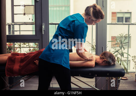 A massage therapist is treating a patient by the window - Stock Photo