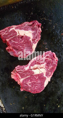 Raw entrecote, of black angus cow meat, on a frying pan - Stock Photo