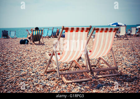 Two deck chairs on a pebble beach - Stock Photo