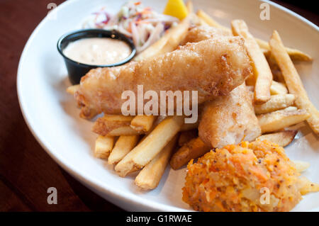 A beautiful prepared fish and chips platter, complete with coleslaw, clapshot and homemade tartar sauce. - Stock Photo