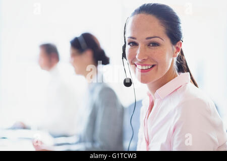 Portrait of smiling businesswoman talking on the phone with headset - Stock Photo