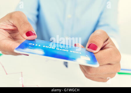closeup of a young caucasian woman, wearing red polished fingernails, with a simulated credit card in her hands, - Stock Photo