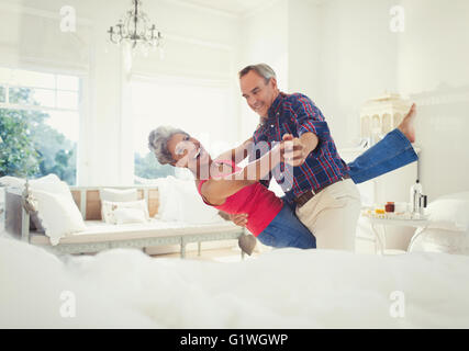 Playful mature couple dancing in living room - Stock Photo