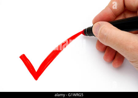 Woman hand with marker drawing red check mark on white background. - Stock Photo