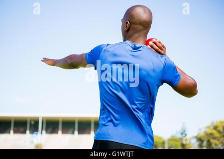 Male athlete preparing to throw shot put ball - Stock Photo