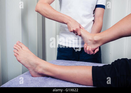 A physiotherapist is treating a patient's foot - Stock Photo