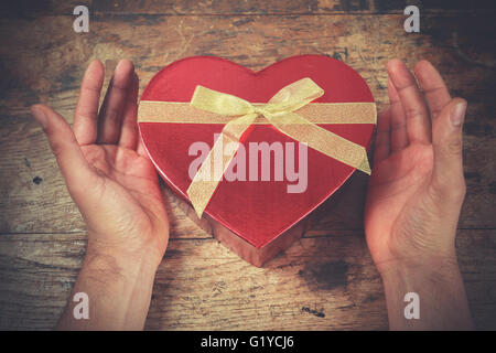 A man's hands are resting on a wooden surface with a heart shaped box - Stock Photo