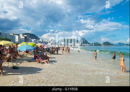RIO DE JANEIRO - FEBRUARY 27, 2016: A rising tide pushes waves closer to beachgoers enjoying an afternoon on Copacabana - Stock Photo