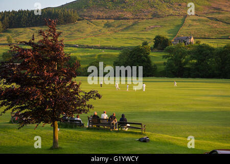 An idyllic, rural setting for spectators to sit and watch a sunny, summer's evening cricket match - Burnsall,  Yorkshire - Stock Photo