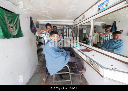 An Indian man pose for camera inside the barber shop in the street of Ajmer, India. - Stock Photo