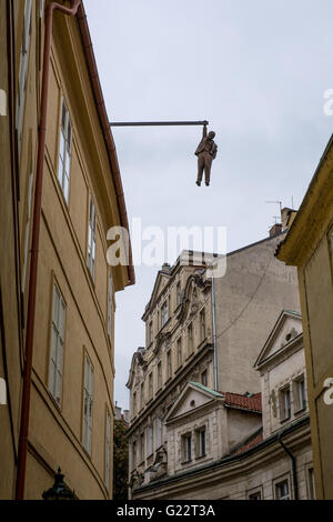 'Man hanging out' sculpture, by David Cerny. Prague, Czech Republic. The sculpture hangs high above the busy streets - Stock Photo