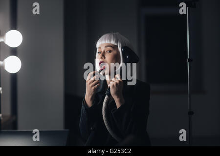 Beautiful bizarre young woman holding steamer and applying lipstick in dressing room - Stock Photo