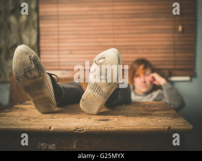 A young woman wearing worn out shoes is resting her feet on a table at home - Stock Photo