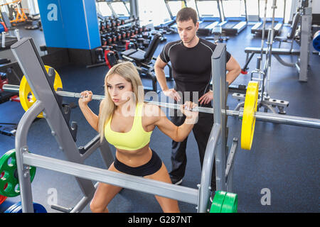 fitness woman and personal trainer in gym - Stock Photo