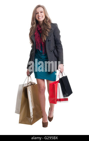 Happy and smiling shopping lady walking and carrying shopping bags in both hands - Stock Photo