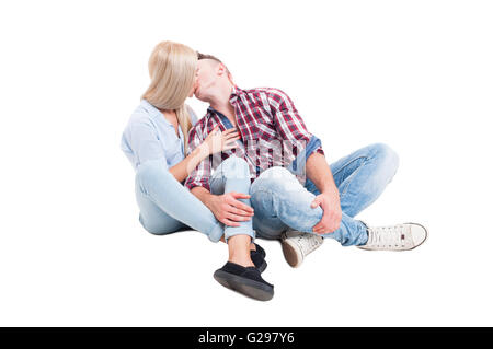 Young couple sitting on white floor and kissing each other isolated on studio background - Stock Photo