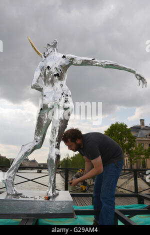 Paris, France. 25th May, 2016. A worker steadies a statue during an exhibition of the iron works by French artist - Stock Photo