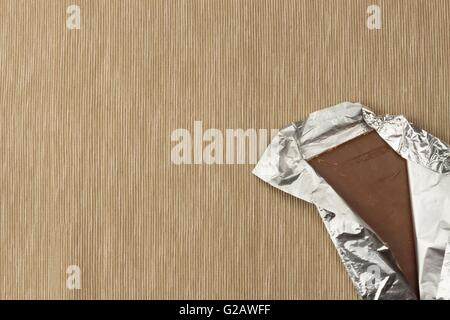 Chocolate wrapped in aluminum foil on bright tablecloth. Advertising on chocolate. Sales chocolate . Packing chocolate - Stock Photo