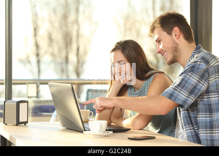 Profile of a happy couple searching information on line together connected in a laptop inside a coffee shop - Stock Photo