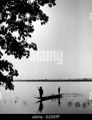 Silhouette of Two Men in Canoe Fishing on River - Stock Photo