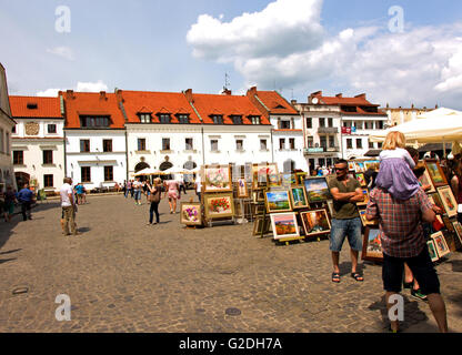 Exhibition of paintings by local artists on the market in Kazimierz Dolny in Poland and tourists walking on the - Stock Photo