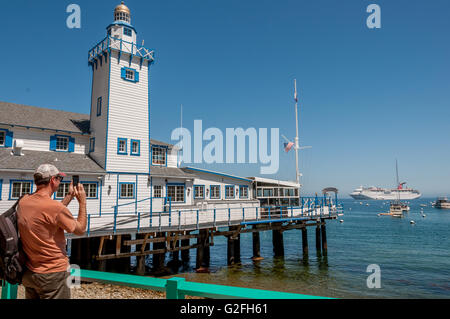 Cruise ship passenger + tourist taking photo on smart phone at Catalina Harbor in Avalon with Carnival Cruise ship - Stock Photo