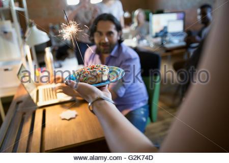 Coworker serving creative businessman birthday donut with sparkler - Stock Photo