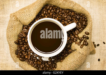 Roasted Coffee Beans In Burlap Bag With Fresh Brewed Coffee On Top - Stock Photo