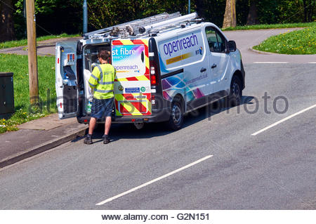 Telephone engineer looking into a white openreach BT van - Stock Photo